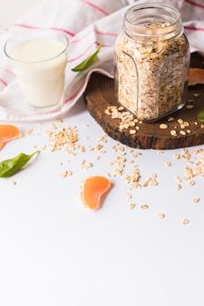 Vaso de leche; hojas de albahaca; avena; rodajas de naranja y servilleta sobre fondo blanco
