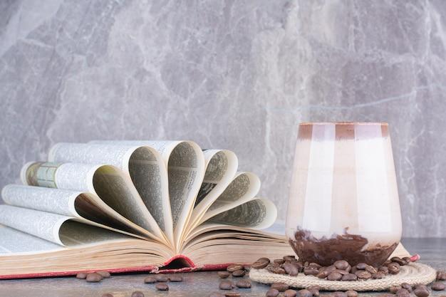 Un vaso de leche con libro abierto y granos de café en mármol