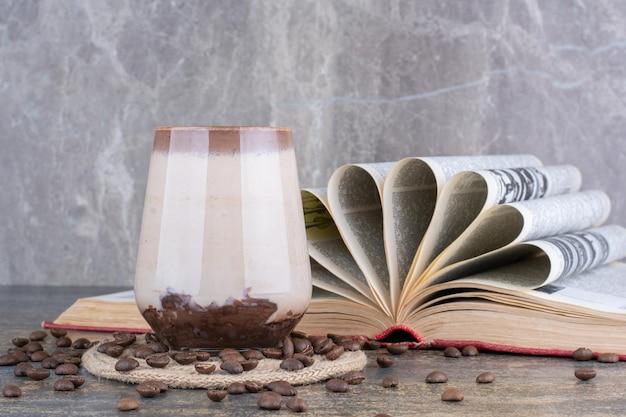 Un vaso de leche con libro abierto y granos de café sobre fondo de mármol. foto de alta calidad