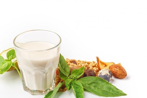 Un vaso de leche y muesli con frutas y hierbas sobre un fondo blanco
