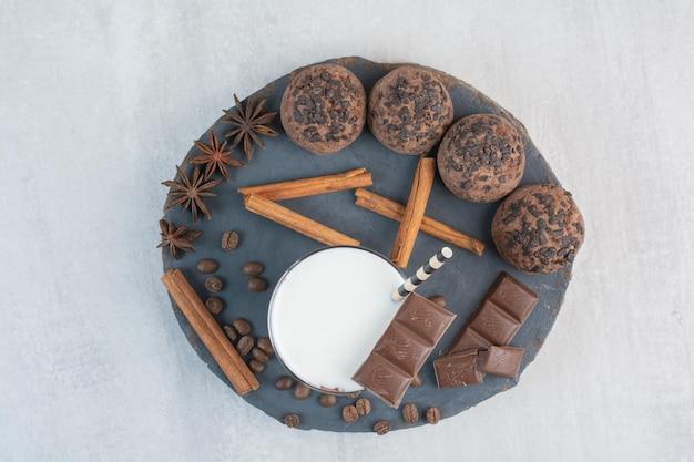 Vaso de leche con paja, chocolate y galletas en pieza de madera. foto de alta calidad