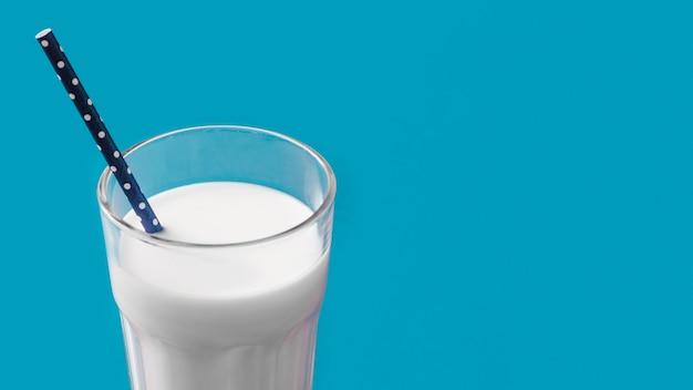 Vaso de leche con pajita sobre fondo azul