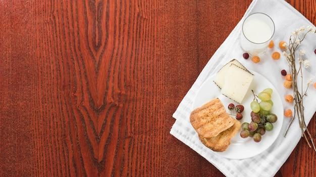Vaso de leche; un pan; rebanada de pastel; uvas; fresa y frambuesa en servilleta blanca sobre mesa de madera