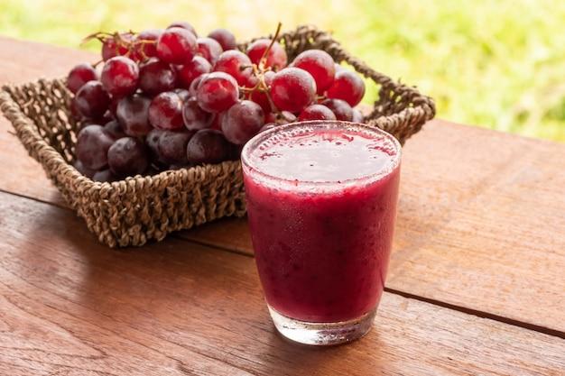 Vaso de licuado de jugo de uva en mesa de madera