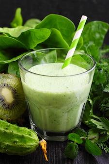 Un vaso de licuado con verduras verdes y espinacas.