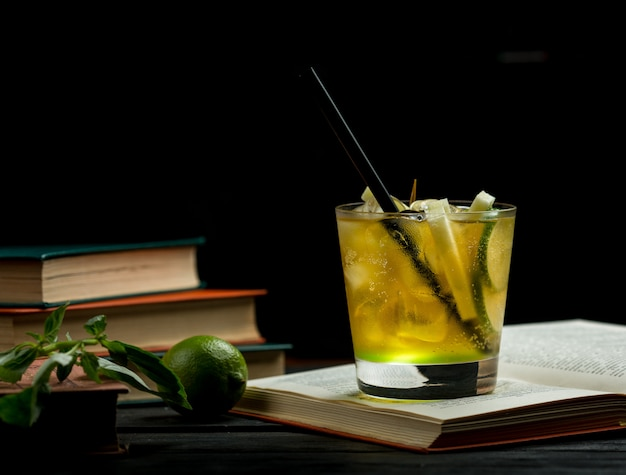 Un vaso de limón, lima, limonada de menta con pipa negra