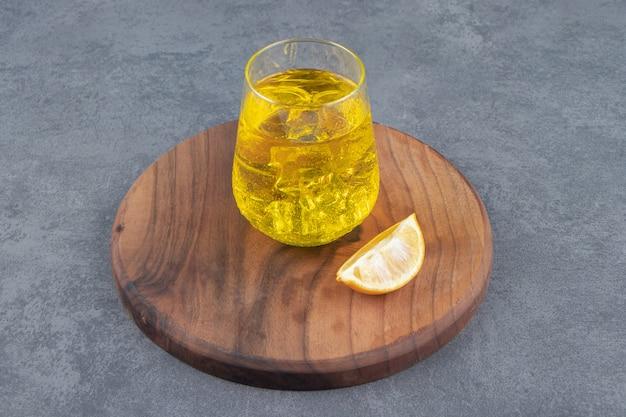 Un vaso de limonada con cubitos de hielo y rodajas de limón.