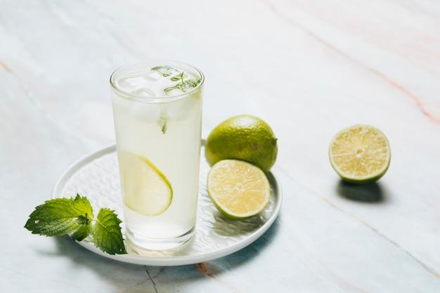 Vaso de limonada y limas sobre fondo de bamble