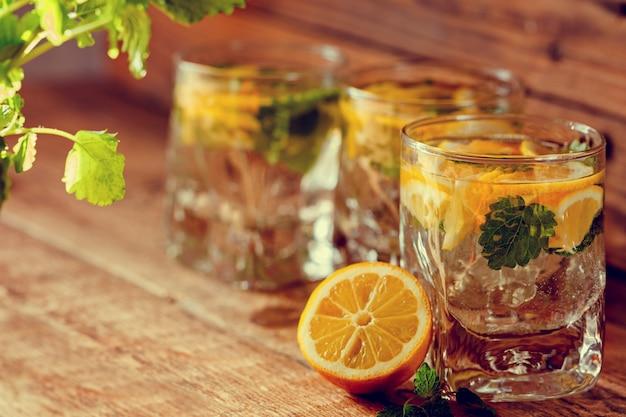 Vaso de limonada con limón fresco y menta sobre fondo de madera
