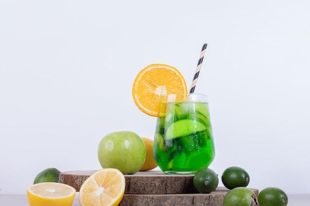 Vaso de limonada con naranja, feijoa sobre plancha de madera