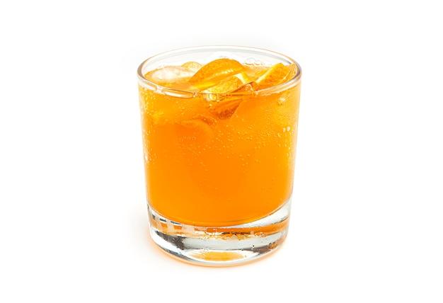 Vaso de limonada naranja con rodajas de fruta y hielo. vista lateral.