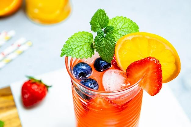 Vaso de limonada refrescante de verano con cóctel de hielo con fresa y limón de cerca
