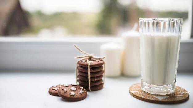 Vaso de líquido blanco cerca de galletas.