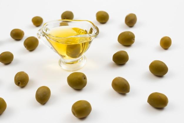 Vaso lleno de aceite rodeado de aceitunas verdes