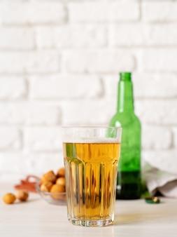 Vaso lleno de botella de cerveza y bocadillos fondo de pared de ladrillo blanco