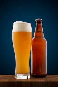 Un vaso lleno de cerveza fría y una botella con cerveza.