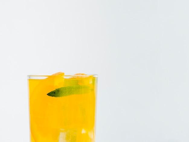 Vaso lleno de jugo de naranja con hielo
