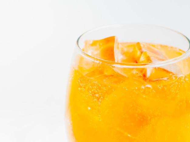 Vaso lleno de refresco de naranja con hielo