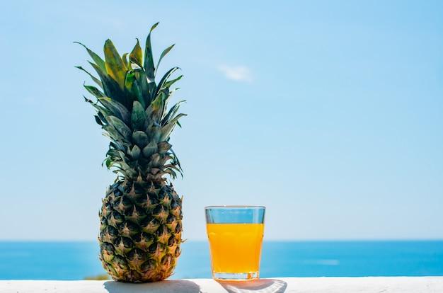 Un vaso lleno de zumo contra el telón de fondo del mar.