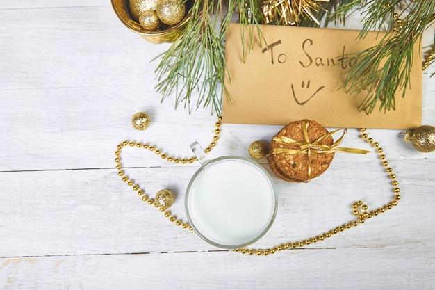Vaso de navidad con leche y galletas para santa en la mesa