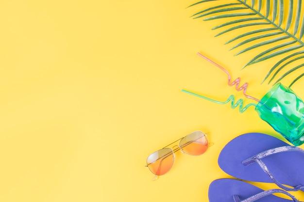 Vaso con pajitas cerca de gafas de sol con chanclas y hojas de plantas.