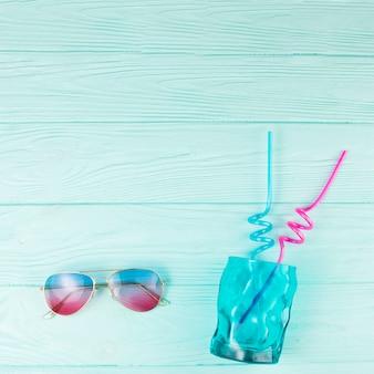 Vaso con pajitas cerca de gafas de sol