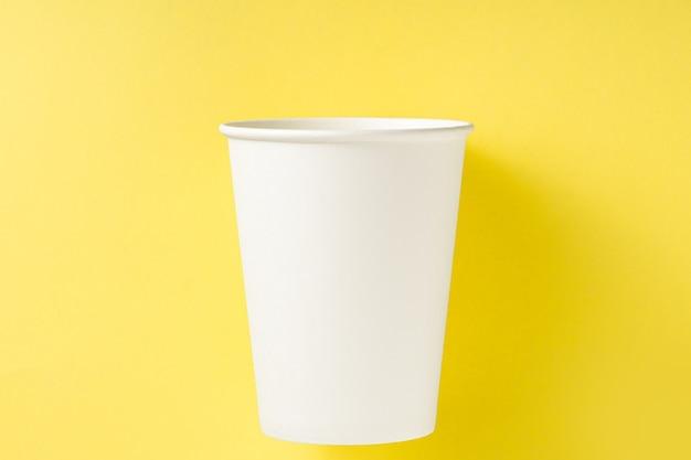 Vaso de papel blanco sobre un fondo amarillo. vista superior concepto de ecología