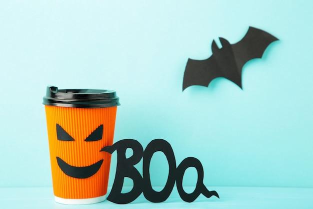 Vaso de papel con cara de halloween en el fondo azul con murciélago de papel negro. vista superior