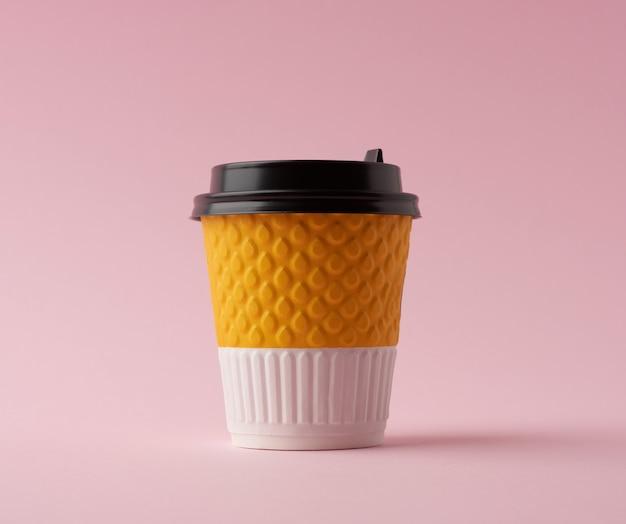 Vaso de papel desechable para bebidas calientes con tapa sobre un fondo rosa