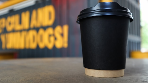 Vaso de papel negro sin texto y logo con café con tapa de plástico sobre una mesa de madera.