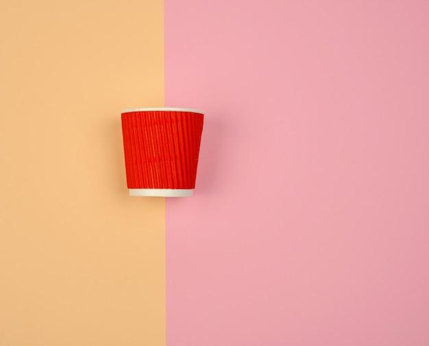 Vaso de papel rojo con bordes corrugados para bebidas calientes.