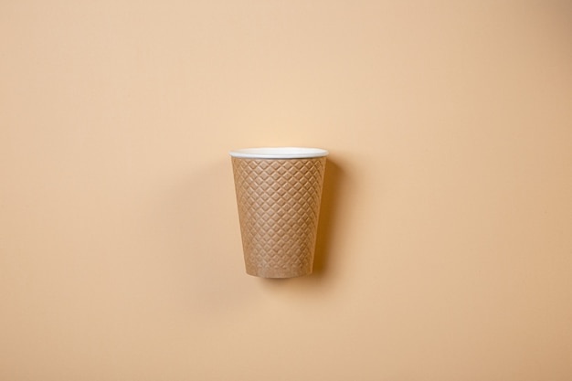 Vaso de papel con textura sobre un fondo crema