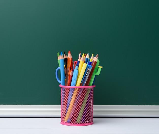 Vaso de papelería rosa con lápices y bolígrafos de madera multicolores, fondo de pizarra, espacio de copia