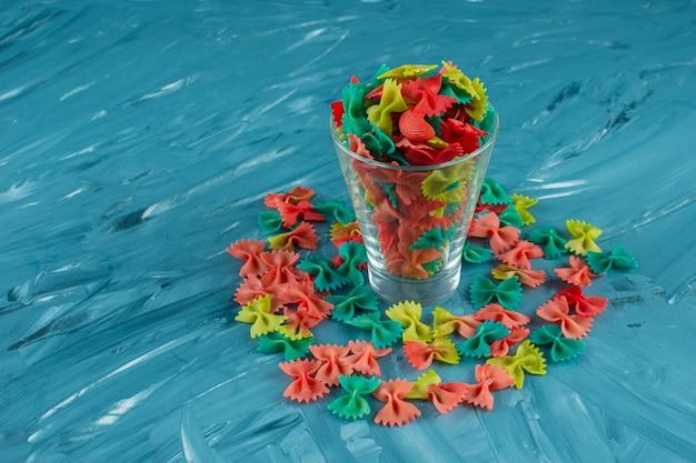 Vaso de pasta farfalle cruda colorida sobre fondo azul.