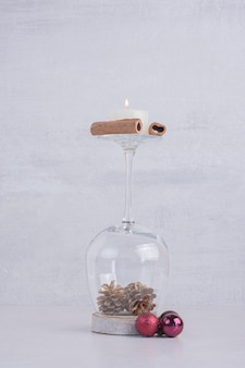 Un vaso de piñas con canela y vela.
