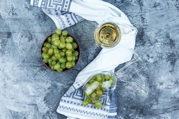 Vaso plano de uvas blancas con vaso de whisky, tazón de uvas, paño de cocina sobre fondo de mármol azul oscuro. horizontal