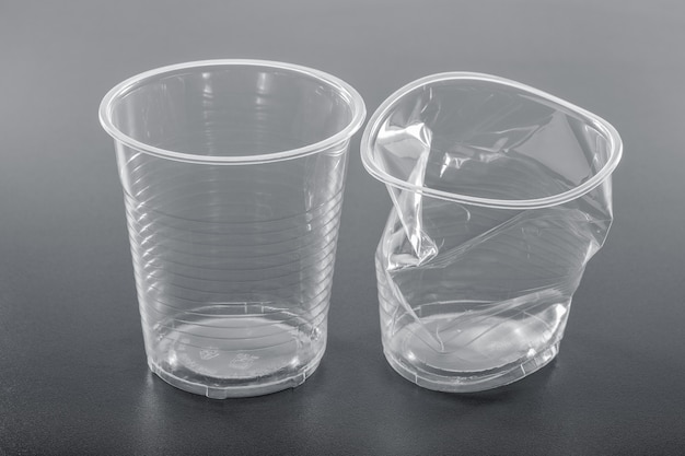 Vaso de plástico blanco liso nuevo y arrugado sobre fondo gris, primer plano. concepto de reciclaje.