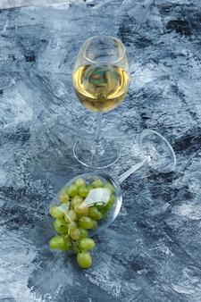 Vaso de primer plano de uvas blancas con vaso de whisky sobre fondo de mármol azul oscuro. vertical