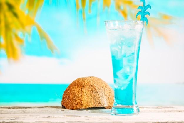 Vaso de refrescante bebida azul y cáscara de coco invertida.