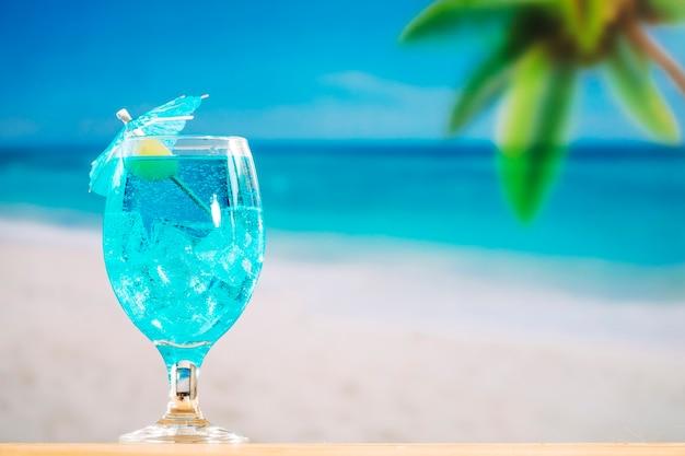 Vaso de refrescante bebida azul decorada con oliva y sombrilla.