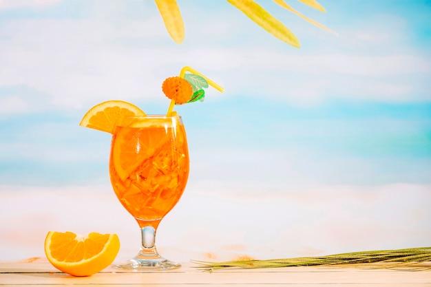 Vaso de refrescante bebida jugosa y rodajas de naranja.