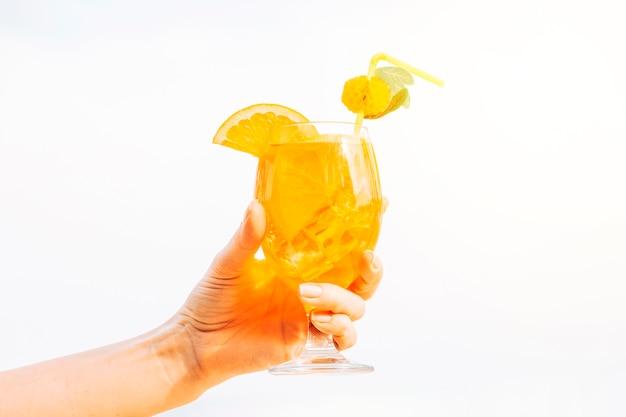 Vaso de refrescante bebida de naranja en la mano