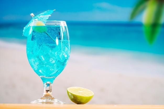 Vaso de refresco bebida azul y rodajas de limón.