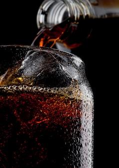 Vaso de refresco de cola fría bebida con cubitos de hielo sobre fondo negro. macro con gotas de rocío.