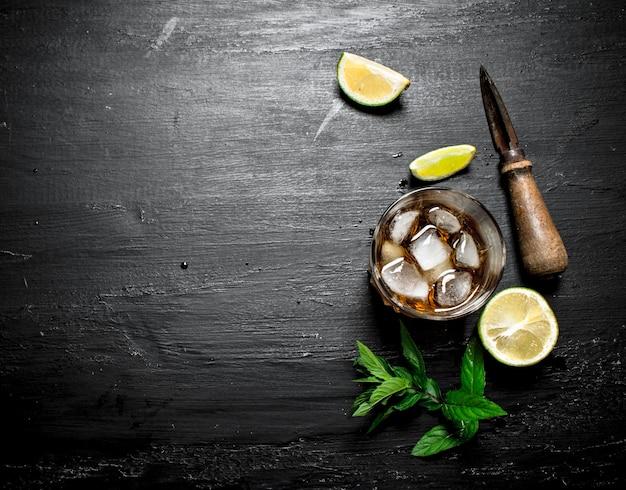 Vaso de ron con limón y menta. sobre un fondo de madera negra.
