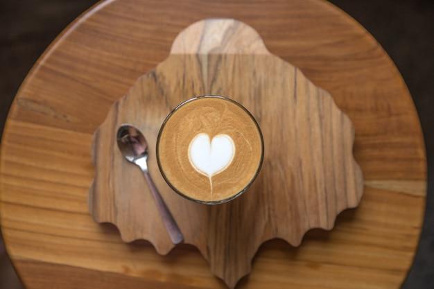 Vaso de sabrosa última con arte de amor en la mesa de madera y escritorio texturizado.
