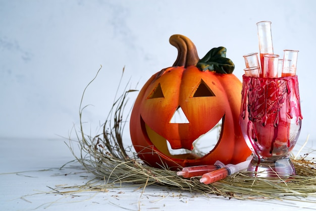 Vaso sangriento de halloween con tubos de ensayo de jugo de tomate y calabaza jack. bebidas de fiesta en pasto seco