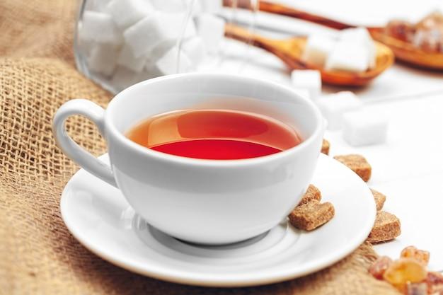Vaso de té caliente con azúcar sobre la mesa