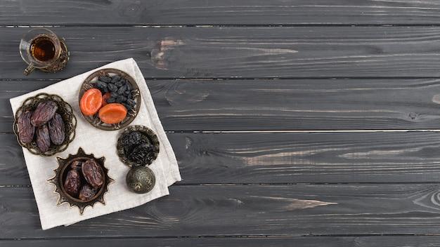 Vaso de té con dátiles enteros y frutas secas en la servilleta sobre el escritorio de madera