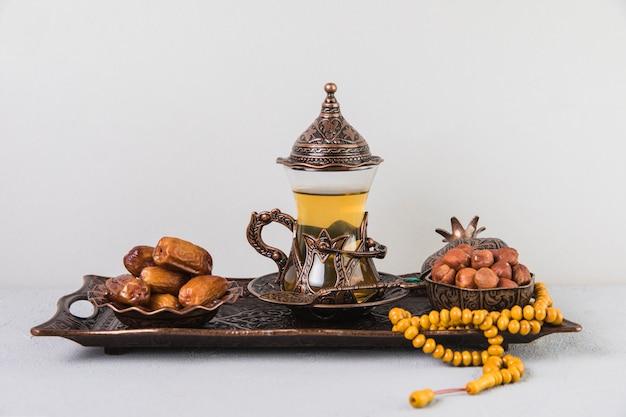 Vaso de té con dátiles frutales y abalorios en bandeja.